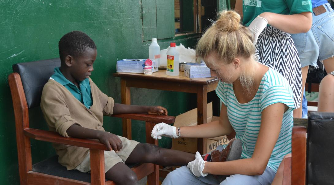A Public Health volunteer treats a boy´s injury in a welfare clinic during her internship with Projects Abroad in Ghana.